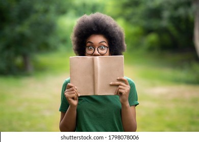 Bookworm. Funny African American Student Girl Standing Outdoors Covering Face With Book, Wearing Glasses, Looking At Camera With Eyes Wide Open