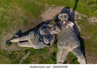 Boom, Antwerp, Belgium 23 July 2021 : Giant wooden troll sculptures statue Una and Joures  lying in a green field of grass in Park de Schorre in Boom, Antwerp, Belgium. Drone aerial top