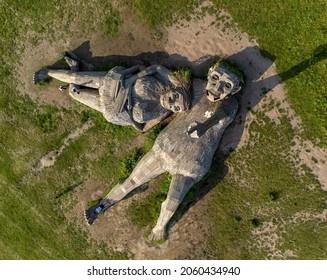 Boom, Antwerp, Belgium 23 July 2021: People standing on Giant wooden troll sculptures Una and Joures by Thomas Dambo in a green field of grass in Park de Schorre in Boom, Antwerp, Belgium.Drone aerial