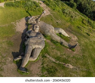 Boom, Antwerp, Belgium 23 July 2021 : Giant wooden troll sculptures statue lying in a green field of grass in Park de Schorre in Boom, Antwerp, Belgium. Una and Joures are the names of the trolls
