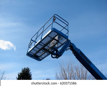 Boom lift reaching high up. Blue elevated work bucket platform, articulating bending arm.
