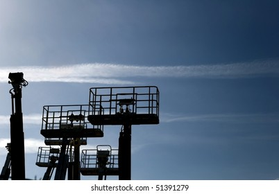 Boom lifts against the sky
