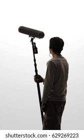 Boom Microphone hold up high by video or film production crew team man and recording sound for movie in a big studio.