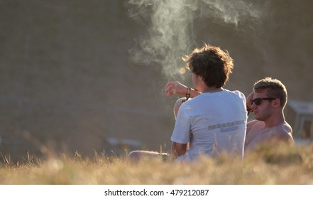 Boomtown Fair Festival - August 14 2016: Two young men lying in a field in a cloud of smoke, smoking at Boomtown Fair, Matterley Bowl, Winchester, Hampshire, August 14 2016, in Hampshire, UK