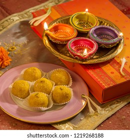 Boondi laddoo- a traditional Indian sweet, gift box and many oil lamps. Deewali festival objects and background.