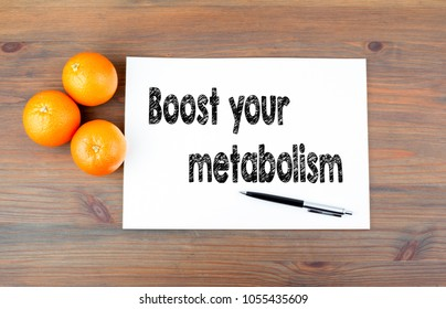 Boost your metabolism. Wooden background with oranges and text