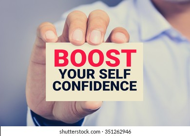 BOOST YOUR SELF CONFIDENCE, message on the card shown by a man, vintage tone