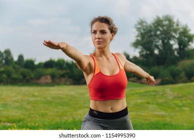Boosting her metabolism. Dark-eyed curly woman boosting her metabolism while going in for sports outdoors
