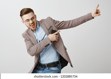 Boosting mood and confidence with right track. Delighted good-looking joyful man with bristle in trendy jacket singing dancing pointing at upper right corner listening music in wireless earbuds