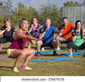 Boot camp fitness trainer yelling during squat exercises
