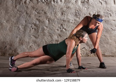 Boot camp training instructor helping lady with push-ups