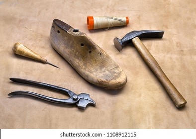 Boot maker tools. Cobbler equipment on leather underlay. Fittings for shoemakers. Awl, straight last, cobbler's hammer, cordwainer's stitch with needle, pliers.