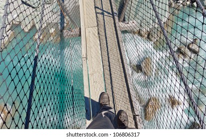 Booted feet of man walking on narrow wooden swing bridge crossing over clear fresh white water rushing through a rocky gorge