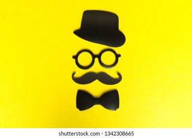 Booth made of cardboard props mustache, hat, glasses isolated on yellow background. Birthday and Party Set
