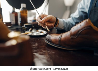 Bootmaker with brush tints shoes, footwear repair