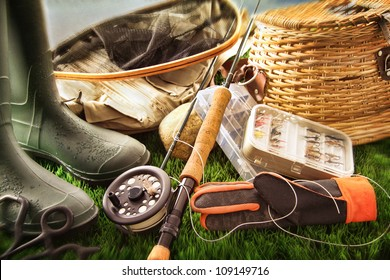 Boots and fly fishing equipment on grass