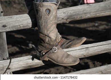 Boots hung with spurs resting on log fence