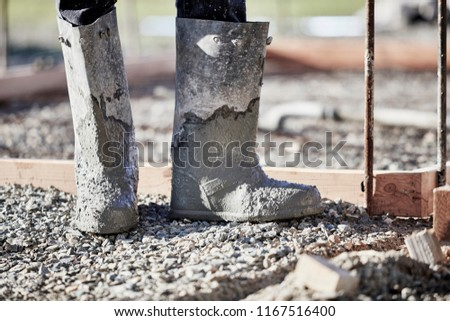 The boots of a mason working in cement with shallow depth of field