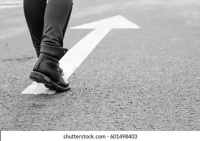 boots on a tarmac road with white direction arrow, the concept of moving forward