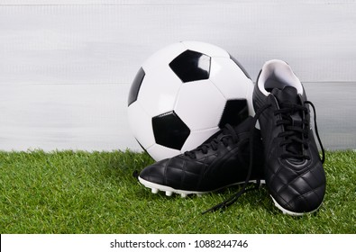 boots, soccer ball, on the grass, on a gray background