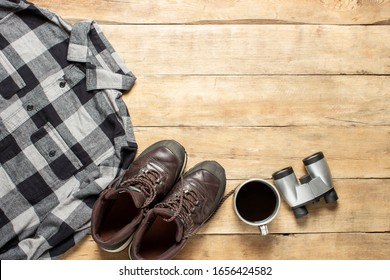 Boots for a trail, shirt, cup with tea, binoculars on a wooden background. The concept of hiking, tourism, camp, mountains, forest. Banner. Flat lay, top view