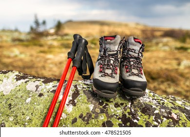 boots and trekking poles on the stone