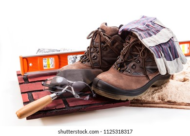 Boots for work, eye protection glasses, gloves and tiles on a white background