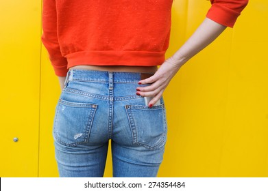 Booty young slim girl in jeans and a red blouse on a yellow background, and the phone in your pocket