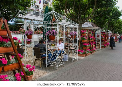 Boppard, Germany - 2015-06-21 Outdoor restaurant and cafe with tables under gazebos  decorated with colorful pink flowers in Boppard, Germany