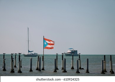 BOQUERON, PUERTO RICO - FEB 23RD, 2016 - The Puerto Rican flag waving in the wind off the shore near a group of moored boats. Puerto Rico officially adopted this flag in 1952.