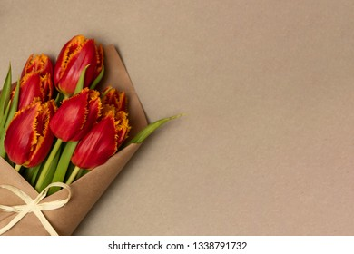 Boquet of red tulips on the cardboard background. Leftside view