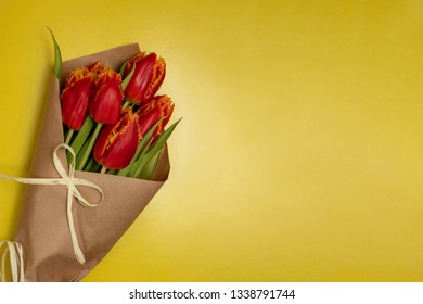 Boquet of red tulips on the yellow background