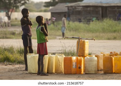 BOR, SOUTH SUDAN-NOVEMBER 1 2013: Unidentified children wait for the water to turn on at a central water point in Bor, South Sudan