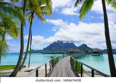 BORA BORA, FRENCH POLYNESIA -7 DEC 2018- View of overwater bungalow villas overlooking the blue lagoon and Mont Otemanu at the Four Seasons Bora Bora resort.