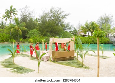 Bora Bora, French Polynesia - January 12 2016: People prepare a traditional wedding ceremony on a beach with palm fronds and bamboo.
