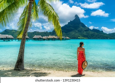 Bora Bora luxury hotel vacation tourist woman relaxing by ocean beach with view of Mt Otemanu in Tahiti, French Polynesia. High End resort with overwater bungalows villas.