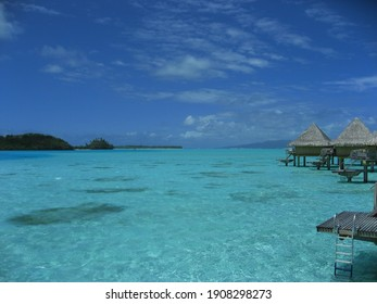 Bora bora, Tahiti with so much sunshine. The shallow sea water is so clear like a swimming pool. The water color gets deeper as they get farther out
