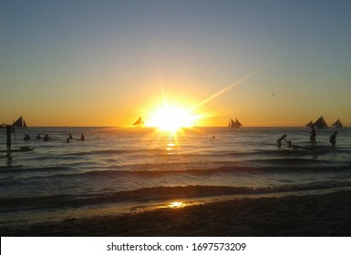 Boracay Island, Aklan / Philippines - March 7, 2016: Breathtaking view of sunset in the world-famous Boracay as tourists enjoy outdoor activities from sailboating, kayaking to simple water dipping.