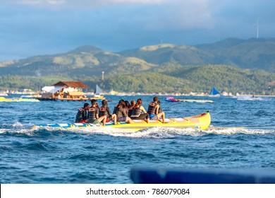 BORACAY ISLAND, PHILIPPINES - November 18, 2017 : Tourists ride a Banana Boat on Boracay sea