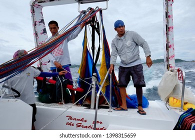 Boracay Island/Philippines- Dec. 2015: Workers are collecting paragliders on yacht boat. Popular entertainment activity in Boracay. Tourists can fly in the sky with pulling force of yachts