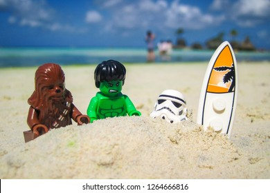 Boracay, Philippines - April 2013: LEGO Hulk and LEGO Chewbacca are burying LEGO Stormtrooper up to the neck in the sand in the beach