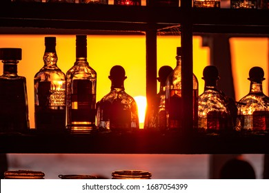 Boracay, Philippines - Jan 21, 2020: Sunset on the background of bottles standing on the bar. The sun passes through the bright glass of the bottles. Background image for the screensaver.