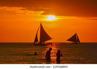 Boracay, Philippines - January 03 2015: tropical island sunset of Boracay in the Philippine sea with sailing boats carrying tourists in the small paradise surrounded by palm trees