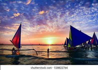 BORACAY, PHILIPPINES - JANUARY 12, 2015 - Several tourists are enjoying the spectacular sunset on the island of Boracay seated on typical Philippines boats.