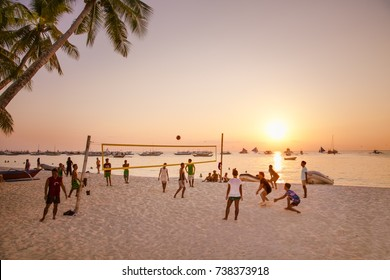 BORACAY PHILIPPINES - MARCH 19, 2016: Unknown people playing beach volleyball at beautiful White beach of Boracay Island on March 19, 2016 in sunset,  Philippines.