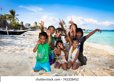 BORACAY, PHILIPPINES-MARCH 20, 2016: Local children near traditional boat at Bulabog Beach on March 20, 2016. Boracay island. Philippines.