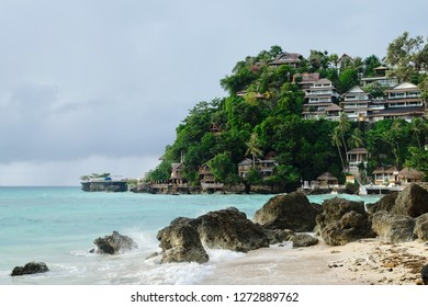 Boracay/phillipens-Dec2015: hotel Villas on green forest mountain near green sea .green trees hill. grey brown rocks sand beach and waves splash foreground. very amazing relax sunny paradise