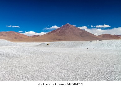 Borax deposits at Laguna Colorada lake with mountain peaks in the background, Bolivia