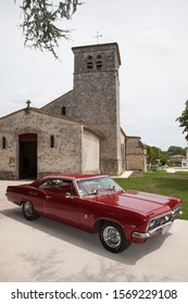 Bordeaux , Aquitaine / France - 11 19 2019 : chevrolet impala red classic american car front old french church