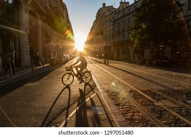 Bordeaux, France - 24th September, 2018: Cyclist crossing the tram tracks at sunset in downtown Bordeaux.